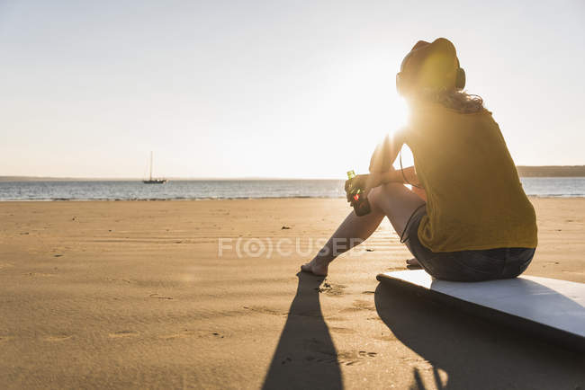 Teenage girl sitting on surfboard and listening music on the beach — Stock Photo