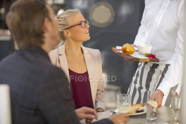 Waiter serving food at table for two — Stock Photo