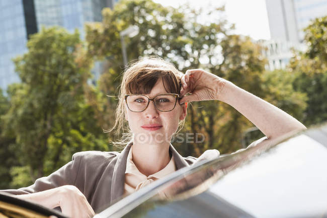 Portrait of businesswoman leaning on car in city — Stock Photo