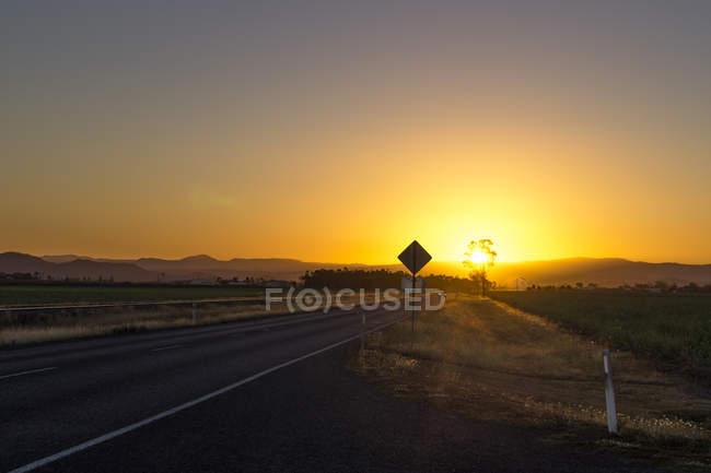 Australie, Queensland, route avec chaîne de montagnes au lever du soleil — Photo de stock