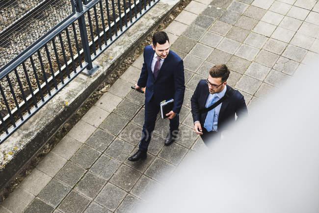 Hommes d'affaires en voyage d'affaires marchant avec des bagages à roues — Photo de stock