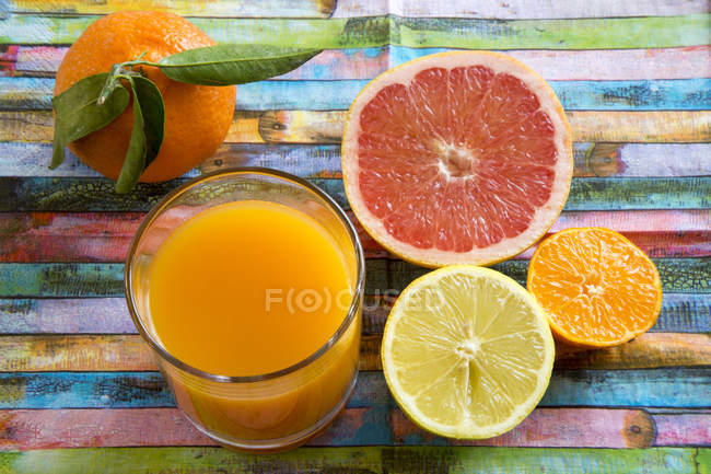 Glass of multivitamine juice and differnet citrus fruits — Stock Photo