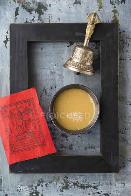 Кубок масло чайного, прапор червоний молитви, чорний фоторамка та Белл на підставі, сірий — стокове фото
