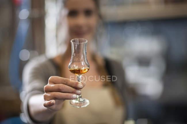 Женщина, держащая бокал для ликера, размытый фон — стоковое фото