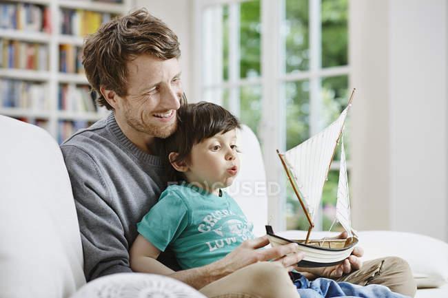 Кавказький батько і син, граючи з іграшкою плаваючому човні — стокове фото