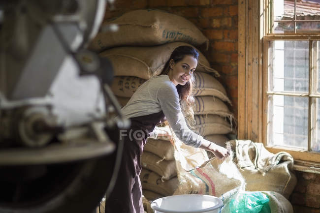 Young woman roasting coffee beans — Stock Photo