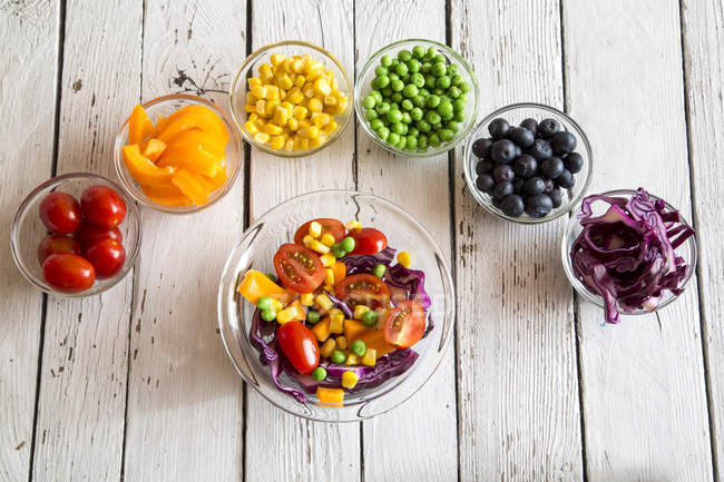 Mixed salad and glass bowls with different raw vegetables rainbow-coloured arranged on white wood — Stock Photo