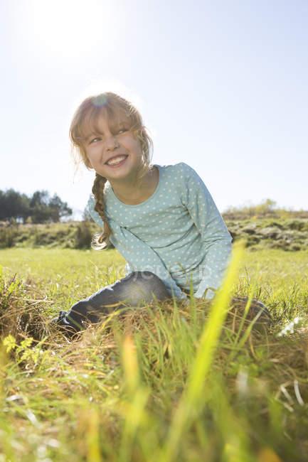 Niña sonriente sentada en un prado en naturaleza - foto de stock