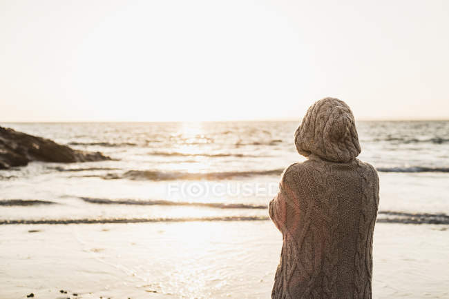 France, Crozon peninsula, woman wearing a cardigan standing on beach at sunset — Stock Photo