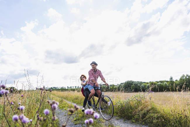 Glückliches junges Paar radelt auf dem Land — Stockfoto
