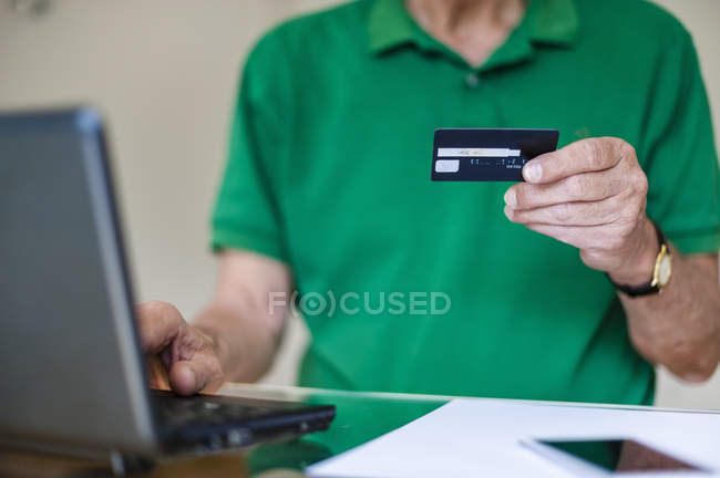 Senior man with laptop and credit card shopping online — Stock Photo