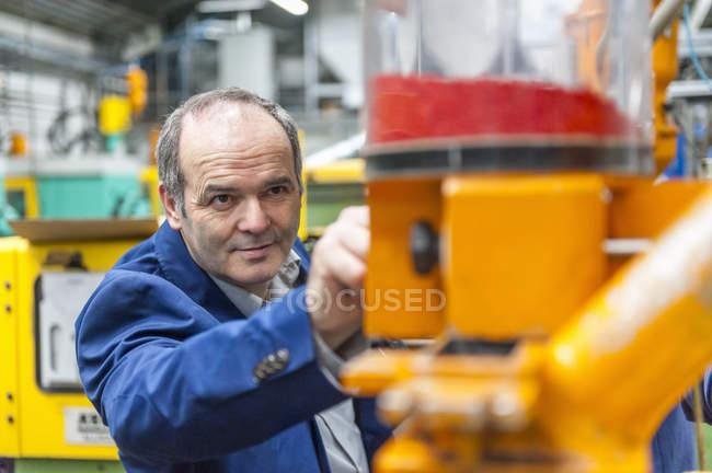 Человек регулирует производственную машину на заводе пластмасс — стоковое фото