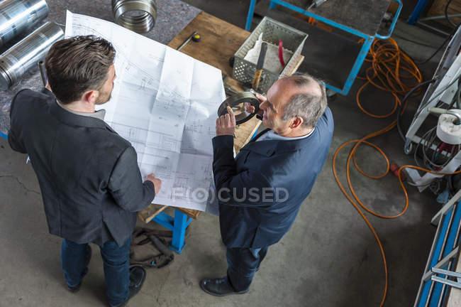 Zwei Ingenieure mit Bauplan im Gespräch, Hydraulikzylinder — Stockfoto