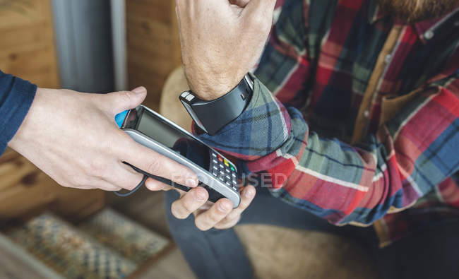 Man paying with smart watch in cafe — Stock Photo