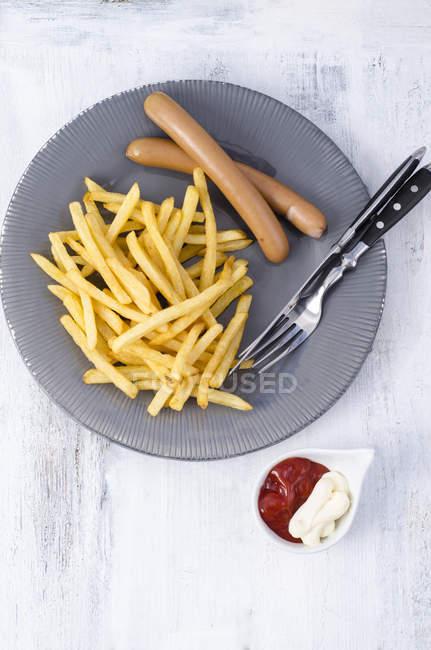 Plato de salchicha y papas fritas y tazón de inmersión de mayonesa y ketchup en madera sobre superficie gris - foto de stock