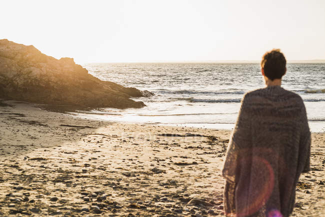 Francia, penisola di Crozon, donna matura in piedi sulla spiaggia al tramonto — Foto stock