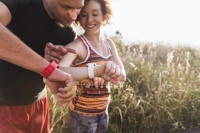 Orologi sportive giovani coppie nel controllo del campo — Foto stock