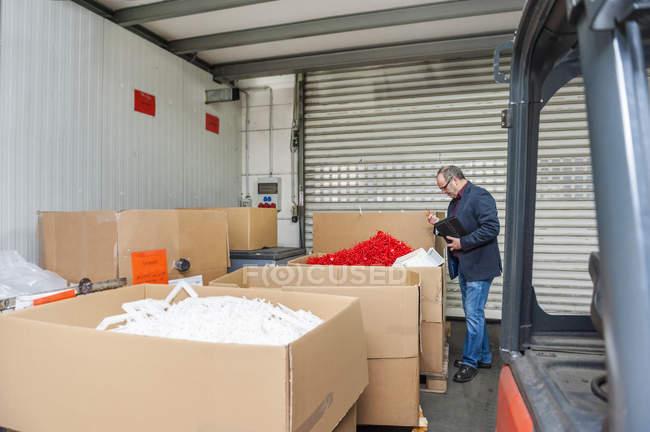 Responsable du stockage des produits de contrôle d'usine en plastique — Photo de stock