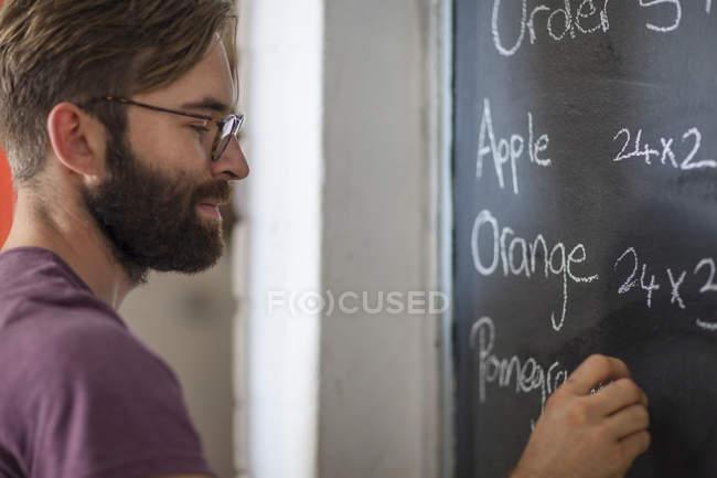 Vista ravvicinata dell'uomo caucasico che scrive sulla lavagna — Foto stock