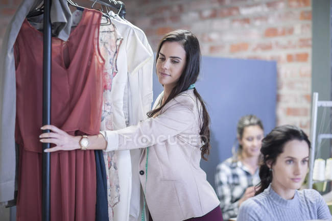 Stilista di moda con stand vestiti nello showroom di moda — Foto stock