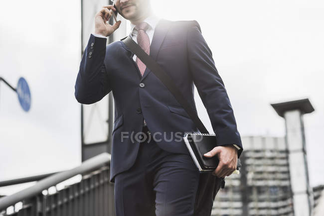 Young businessman standing at railing and using smartphone — Stock Photo