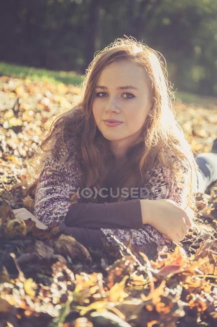 Портрет девочки-подростка, лежащей на земле, покрытой осенней листвой — стоковое фото