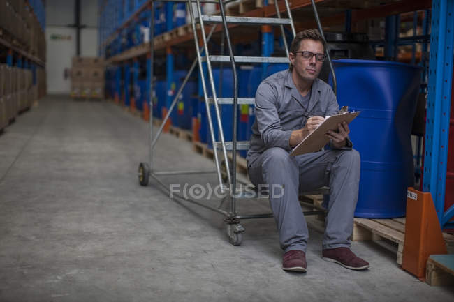 Travailleur masculin caucasien faisant le point dans l'entrepôt — Photo de stock