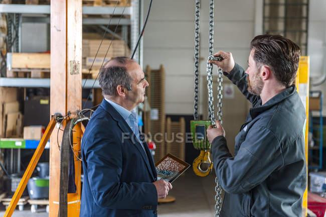 Manager und Arbeiter in der Werkstatt, Hebezeug — Stockfoto