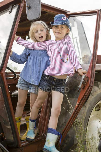 Retrato de dos niñas sonrientes de pie en el tractor - foto de stock