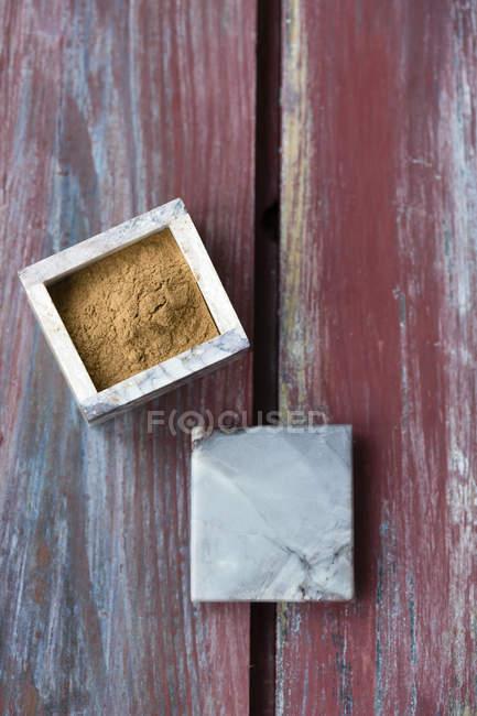Pequena caixa de canela em pó na superfície de madeira — Fotografia de Stock