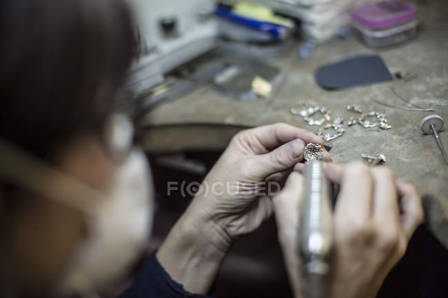 Closeup view of goldsmith working on jewlery in workshop — Stock Photo