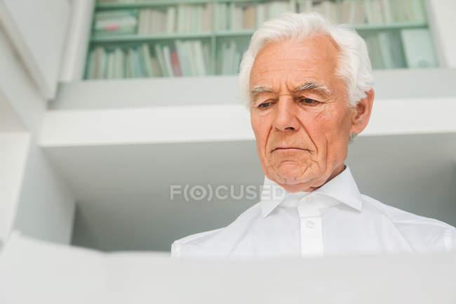 Porträt eines älteren Mannes bei der Prüfung eines Dokuments — Stockfoto