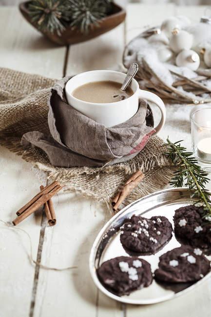 Чашка чая Масала с миндальным молоком и шоколадным печеньем с корицей на дереве — стоковое фото
