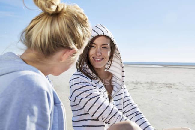 Два подруг разом сидячи на пляжі — стокове фото