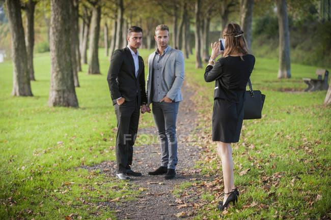 Молодой предприниматель, фотографирование бизнес партнеров с ее smartphone в парке — стоковое фото