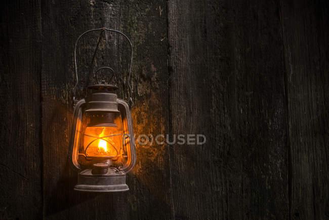 Iluminado lanterna de gás velho pendurado na parede de madeira — Fotografia de Stock