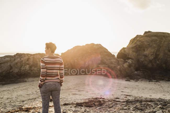Donna matura che sta alla spiaggia e godersi il tramonto — Foto stock
