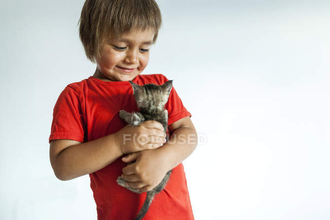 Ritratto di bambino sorridente che tiene in braccio il gattino — Foto stock