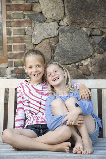 Porträt zweier lächelnder Mädchen auf einer Bank — Stockfoto