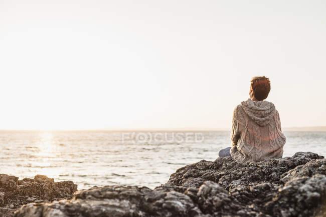 Donna che si siede sulla roccia in spiaggia e tramonto godendo — Foto stock