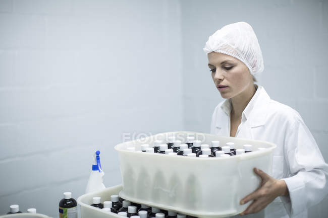 Woman carrying box of medical supplies in medical factory — Stock Photo