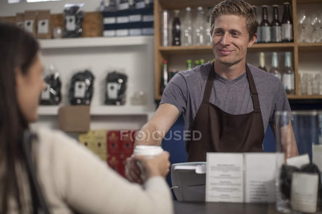 Man in a cafe handing over disposable coffee cup — Stock Photo