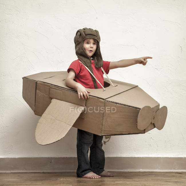 Little boy playing with pilot hat and cardboard box aeroplane — Stock Photo
