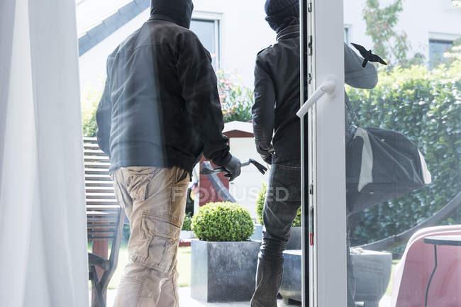 Днем два грабителя покидают дом с добычей. — стоковое фото
