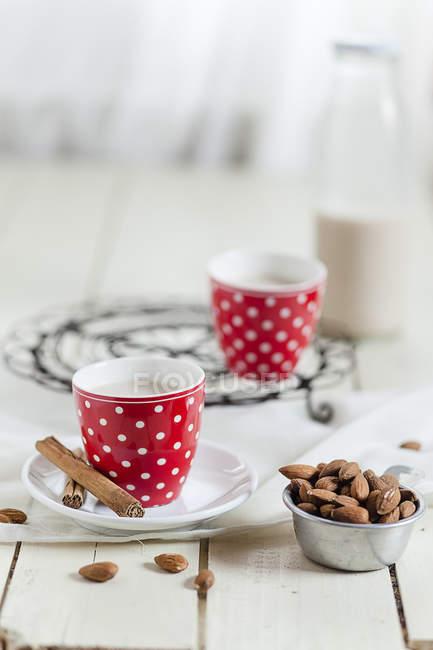 Две чашки домашнего миндального молока, коричные палочки и миска миндаля — стоковое фото