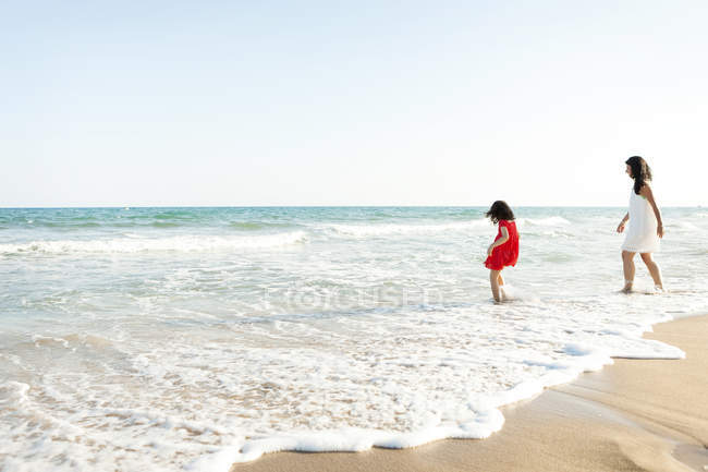 Little girl and her mother walking at seafront on the beach — Stock Photo