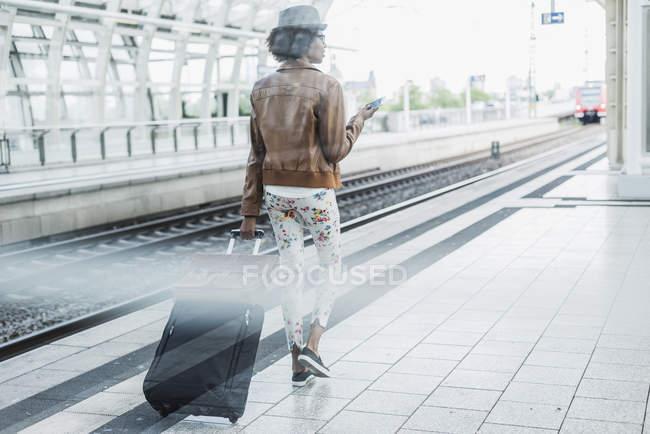 Visão traseira da jovem com smartphone e bagagem na plataforma — Fotografia de Stock