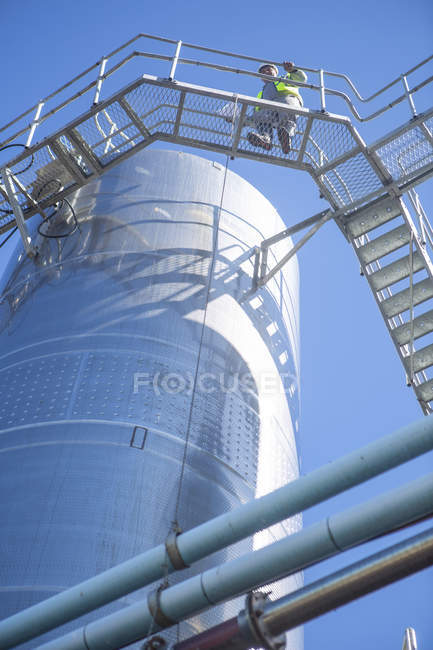 Worker controlling stainless steel tanks for food industry — Stock Photo