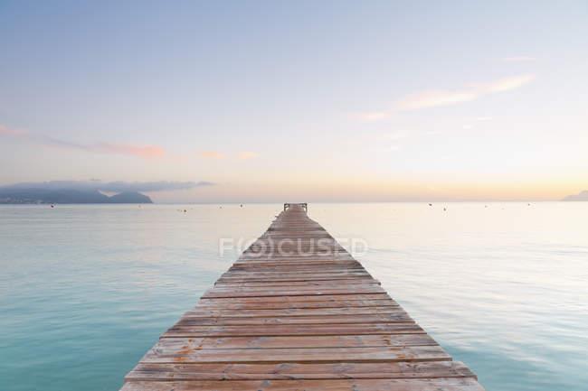 Испания, Балеарские острова, Майорка, причал выходит в море при утреннем свете — стоковое фото