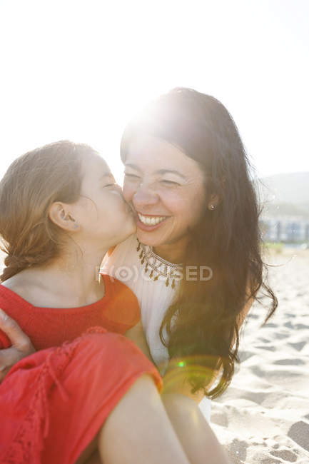 Little girl kissing her mother on the beach — Stock Photo